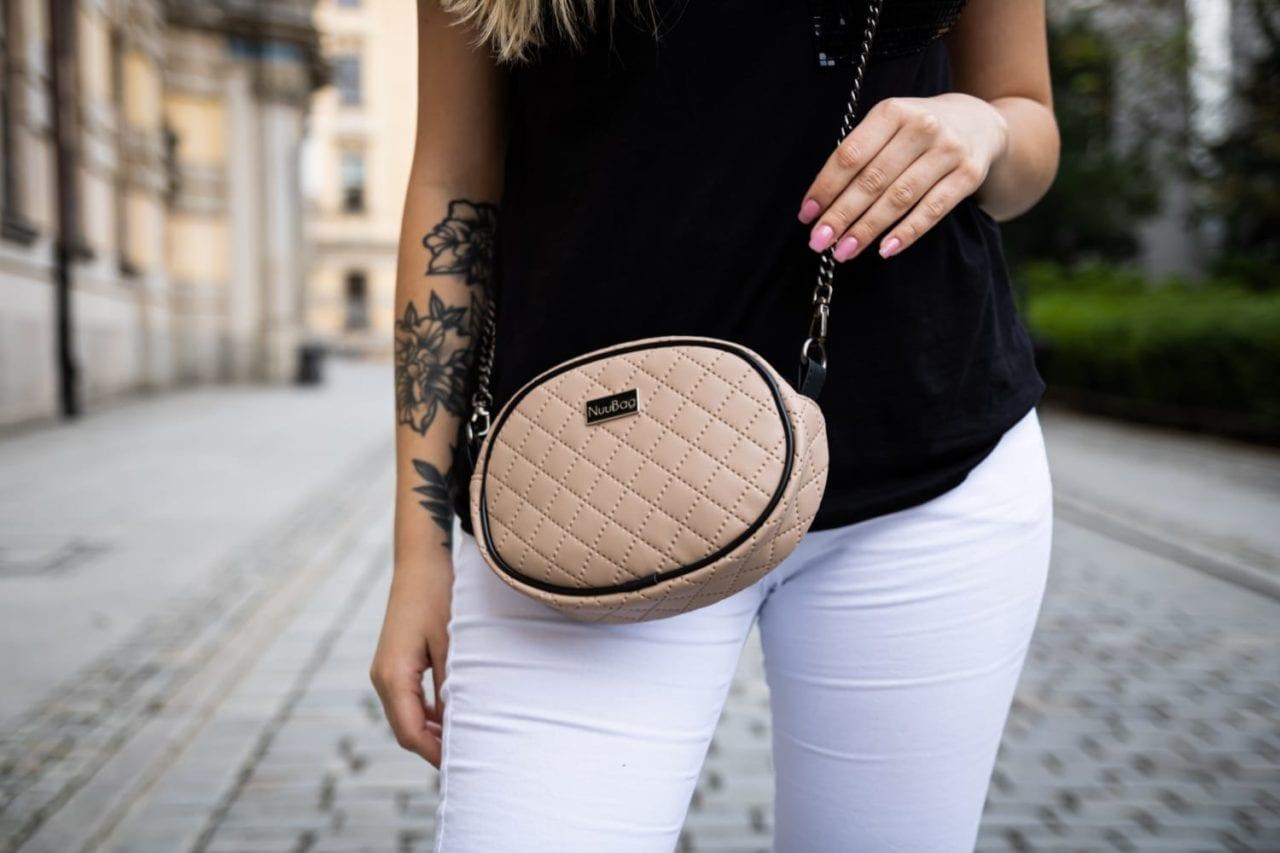 Beżowa torebka na łancuszku. Zdjęcie z modelką.