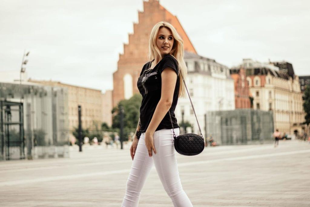 Czarna torebka na łańcuszku. Zdjęcie z modelką.